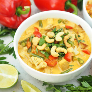 one bowl of curry with peppers and limes