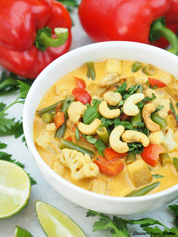 bowl of curry with peppers and limes