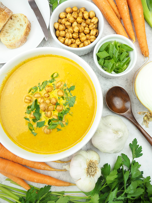 Curried Carrot Soup with bread, chickpeas, scallions, carrots, garlic, parsley, and spoon