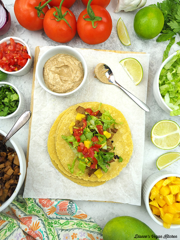 Seitan Taco with bowls of ingredients and aioli
