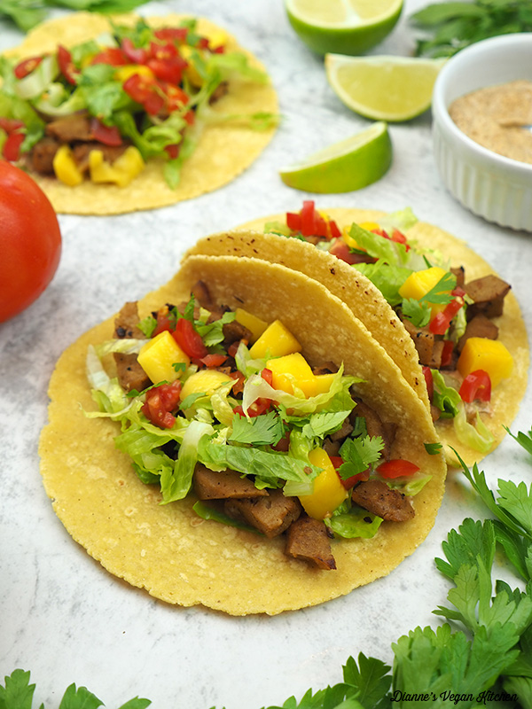 two tacos with limes and aioli