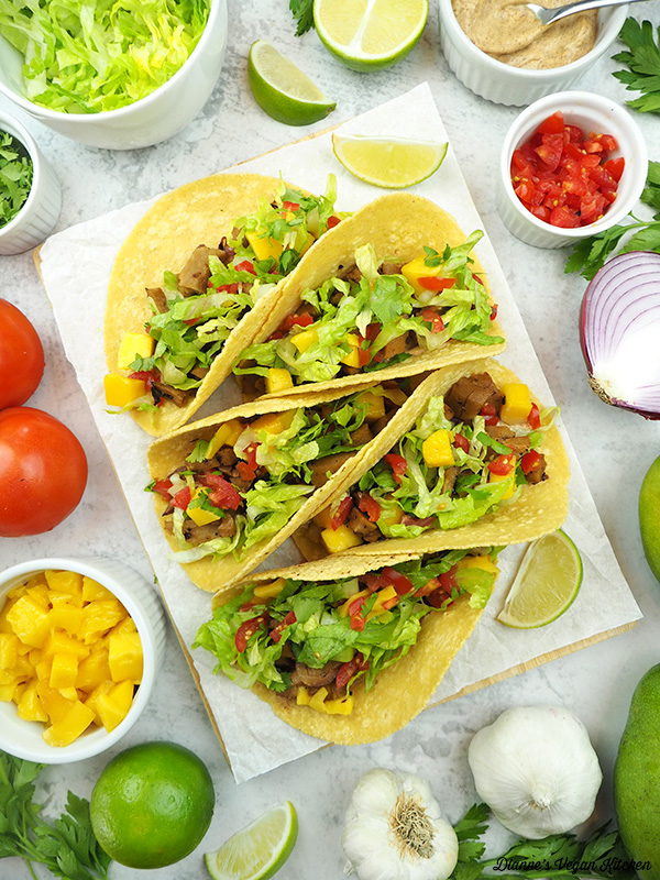 Seitan Tacos with bowls of toppings, mangos, garlic, onion, limes, and tomatoes