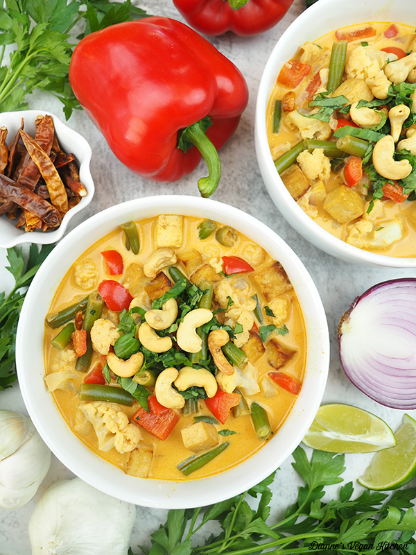 two bowls of curry with peppers, onion, and lime