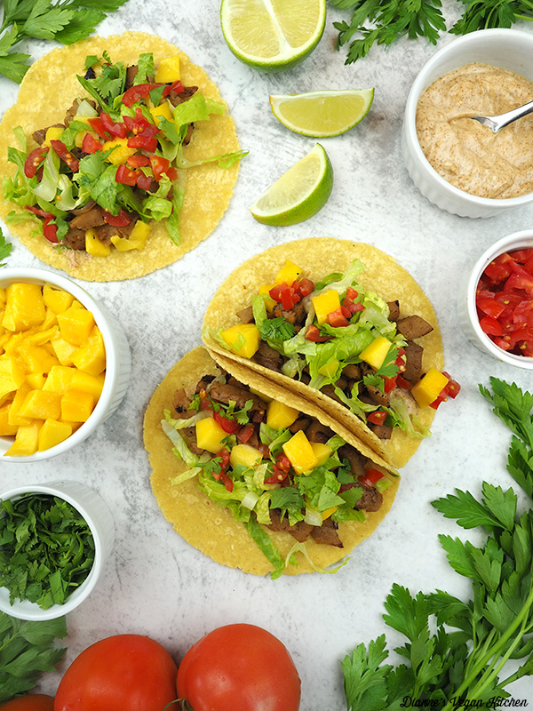 two tacos with limes, tomatoes, mango, cilantro, and aioli