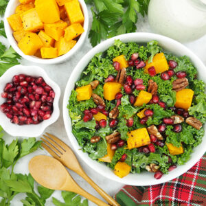 holiday kale salad with dressing, squash, and pomegranate seeds square
