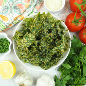 bowl of kale chips with tomatoes, lemon, chives, garlic, and sesame seeds
