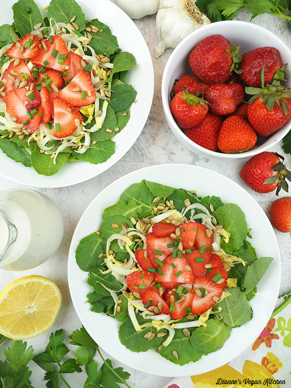 two bowls of salad with strawberries, dressing, and lemon