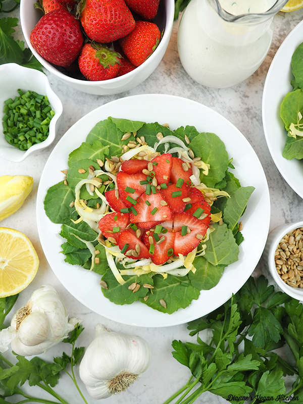 bowl of salad with strawberries, dressing, and lemon